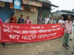 "Activists of Gonoshanghati Andolon, a leftist political organization, are waiting for their other comrades beside the Dhaka-Dinajpur highway. The banner says: ""No openpit coal mining, No MNOC, No export, Red salute to the martyrs of the movement to protect national resources."""
