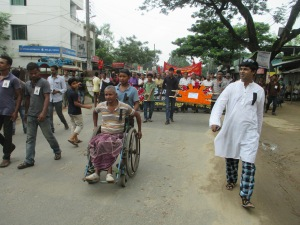 Bablu Roy who was shot to the spinal cord on 26 August 2006 by the armed force of the state is leading the rally of Central National Committee on his wheel chair. He looks forty something in his thirties.