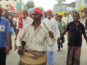 A santal man plays his dhol in the rally.